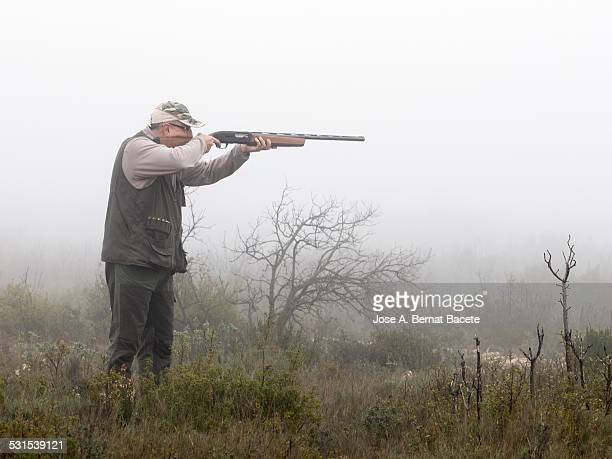 Hunter appearing with his shotgun on a foggy day