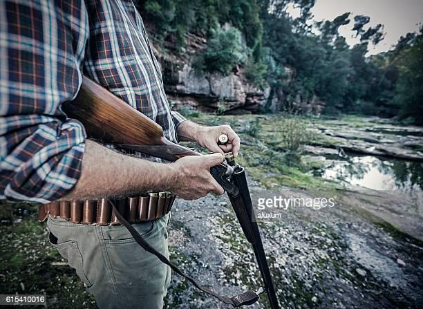 Hunter charging his shotgun during bird hunting