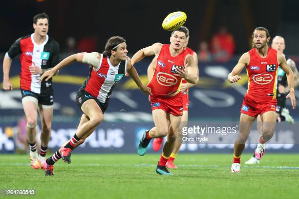 Hunter Clark of the Saints and Ben Ainsworth of the Suns run for the ball during the round 10 AFL match between the Gold Coast Suns and the St Kilda...