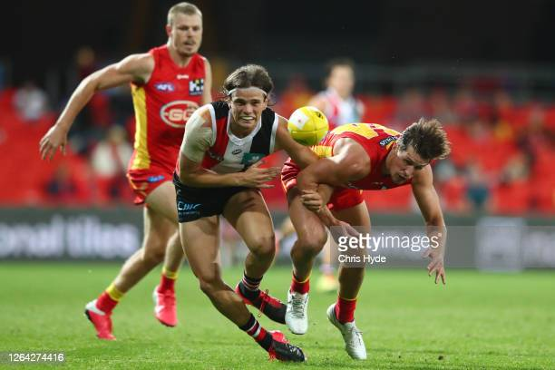 Hunter Clark of the Saints and David Swallow of the Suns run for the ball during the round 10 AFL match between the Gold Coast Suns and the St Kilda...