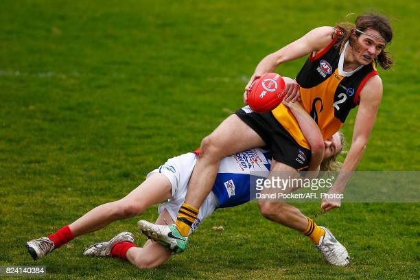 Hunter Clark of the Stingrays is tackled by Bailey Beck of the Power during the round 14 TAC Cup match between Dandenong and Gippsland at Frankston...