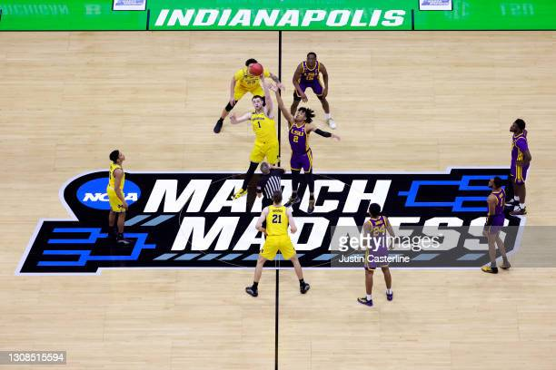 Hunter Dickinson of the Michigan Wolverines and Trendon Watford of the LSU Tigers jump for the opening tip during the first half in the NCAA...