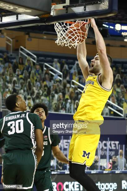 Hunter Dickinson of the Michigan Wolverines dunks past Marcus Bingham Jr. #30 of the Michigan State Spartans during the second half at Crisler Arena...