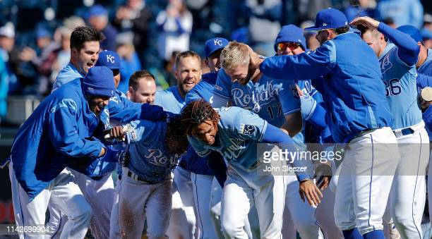 Hunter Dozier and Terrance Gore of the Kansas City Royals celebrate with teammates after Dozier hit the game winning single to score Gore from third...