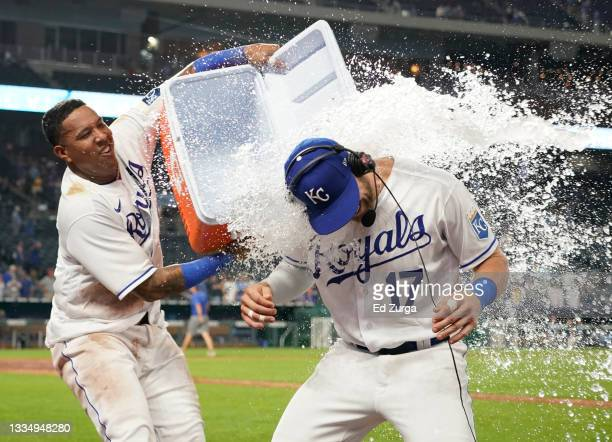 Hunter Dozier of the Kansas City Royals is doused with water by Salvador Perez as they celebrate a 3-2 win over the Houston Astros at Kauffman...