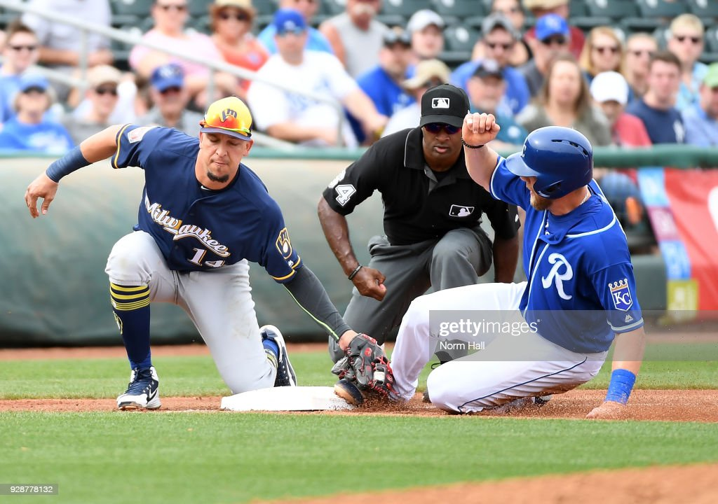 Hunter Dozier #17 of the Kansas City Royals is tagged out while attempting to steal third base by Hernan Perez #14 of the Milwaukee Brewers as third base umpire Alan Porter #64 looks on during the fourth inning of a spring training game at Surprise Stadium on March 7, 2018 in Surprise, Arizona.