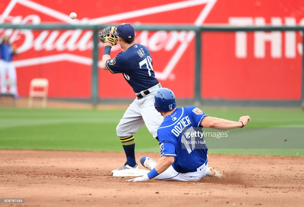 Hunter Dozier #17 of the Kansas City Royals safely slides into second base after hitting double to left field as Nate Orf #70 of the Milwaukee Brewers waits for the throw while covering the bag during the fourth inning of a spring training game at Surprise Stadium on March 7, 2018 in Surprise, Arizona.