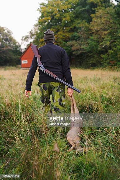 hunter dragging deer through field - dead deer stock photos and pictures
