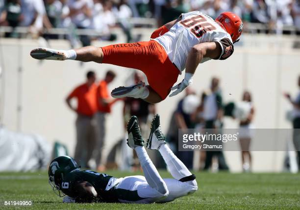 Hunter Folkertsma of the Bowling Green Falcons flies over the tackle of David Dowell of the Michigan State Spartans at Spartan Stadium on September 2...