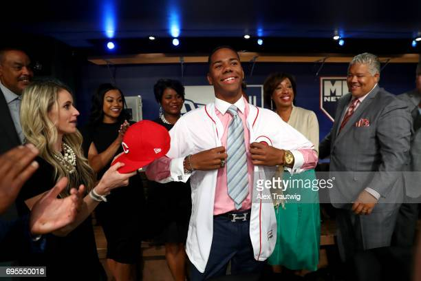 Hunter Greene puts on a Cincinnati Reds jersey after being selected second overall by the Reds during the 2017 Major League Baseball Draft at Studio...