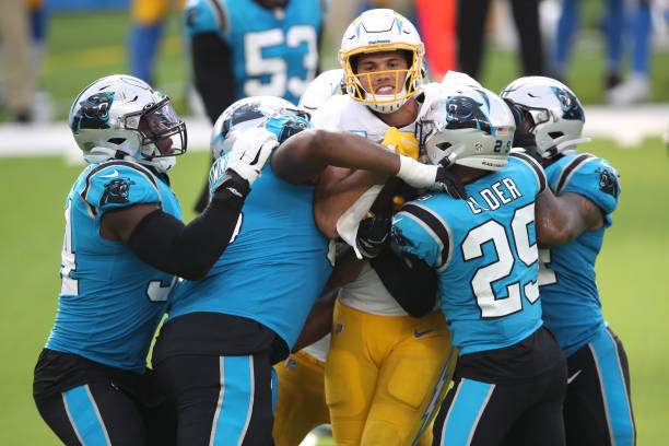 Hunter Henry of the Los Angeles Chargers is wrapped up on a pass play by Corn Elder of the Carolina Panthers during the second half of a game at SoFi...