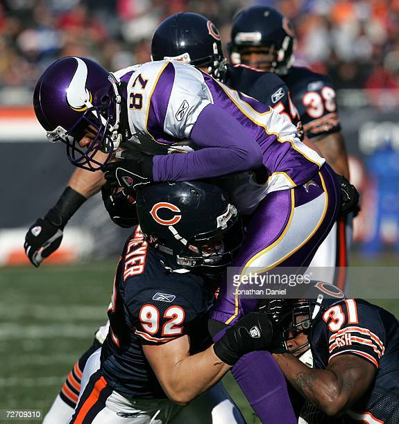 Hunter Hillenmeyer Nathan Vasher and Brian Urlacher of the Chicago Bears tackle Marcus Robinson of the Minnesota Vikings on December 3 2006 at...