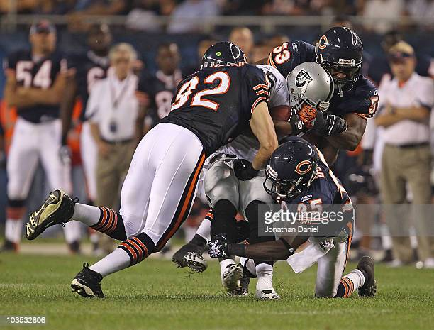 Hunter Hillenmeyer Nick Roach and Zack Bowman of the Chicago Bears bring down Rock Cartwright of the Oakland Raiders during a preseason game at...