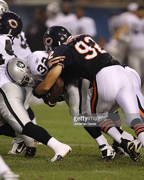Hunter Hillenmeyer of the Chicago Bears tackles Michael Bennett of the Oakland Raiders during a preseason game at Soldier Field on August 21 2010 in...