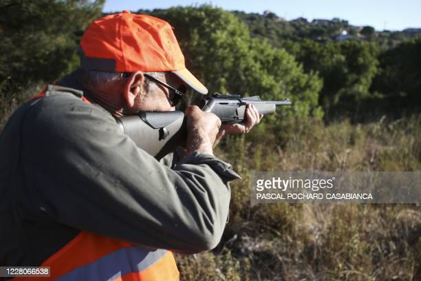 Hunter holds his gun during a boar hunt in Pietrosella on the French Mediterranean island of Corsica, on August 15, 2020.