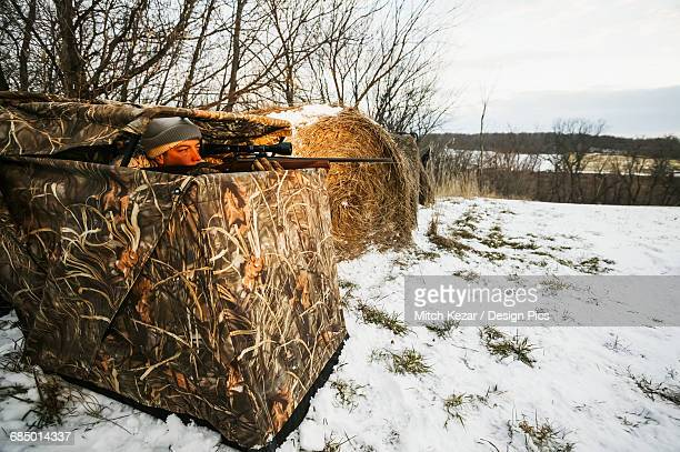 Hunter In Pop Up Blind in the Snowy Winter While Hunting Whitetail