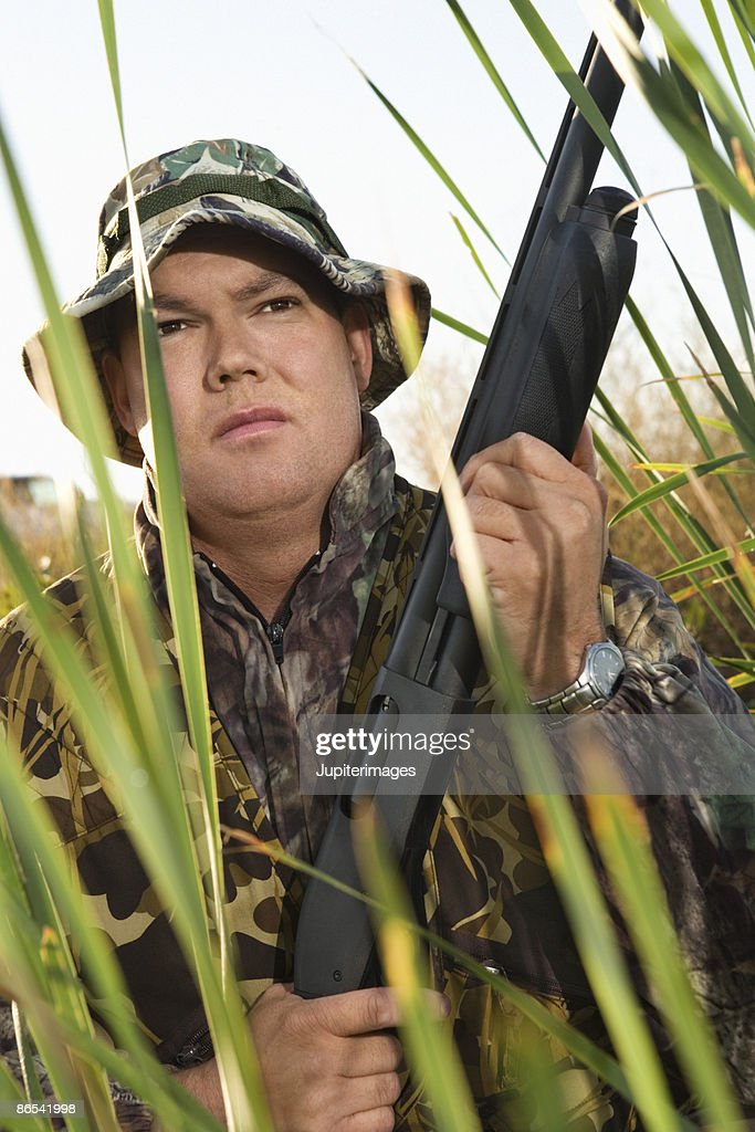 Hunter in reeds with rifle : Stock Photo