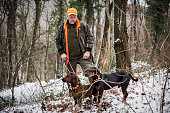 hunter forest with rifle hunting dogs