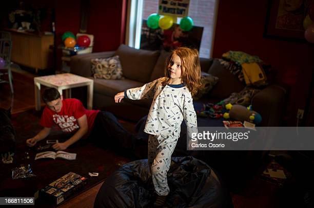 Hunter Kemp balances on a bean bag with his brother Josh Hofley builds a Lego toy Hunter received at the party Hunter Kemp who was featured in the...
