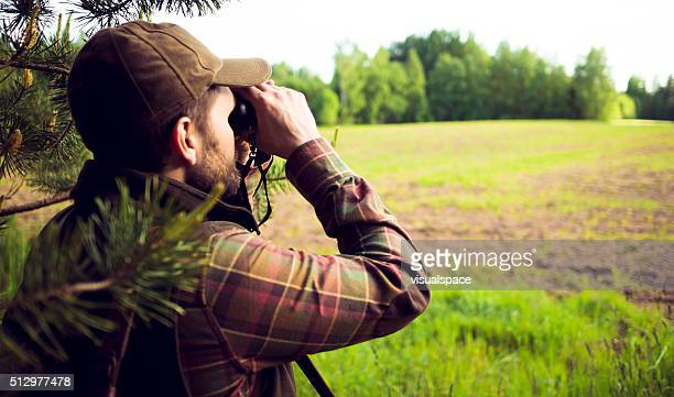 hunter looking over the field through binoculars - hunting stock pictures, royalty-free photos & images