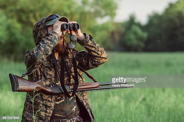 Hunter looking through binoculars on grassy field