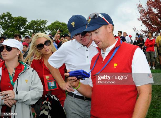 Hunter Mahan and Brandt Snedeker of the US Team watch the action on FanVision device while Kandi Mahan and Mandy Snedeker looks on during the Final...