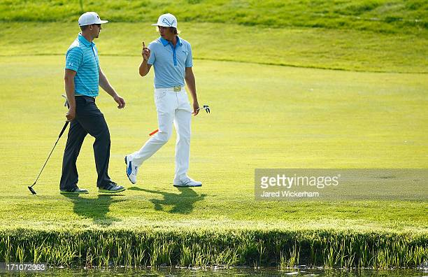 Hunter Mahan and Rickie Fowler talk while walking to the 18th green during the second round of the 2013 Travelers Championship at TPC River Highlands...