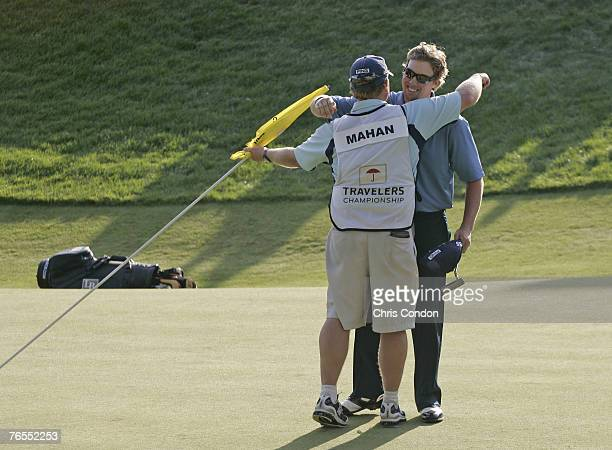 Hunter Mahan hugs his caddie after Mahan won the playoff during the fourth and final round of the Travelers Championship held at TPC River Highlands...