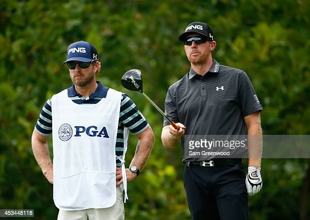 Hunter Mahan of the United States waits on the fourth tee with caddie John Wood during the final round of the 96th PGA Championship at Valhalla Golf...