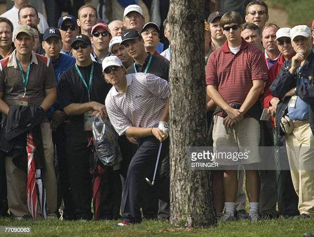 Hunter Mahan of the US hits his second shot from behind a tree on the 2nd hole during the fourball matches at The Royal Montreal Golf Club host of...