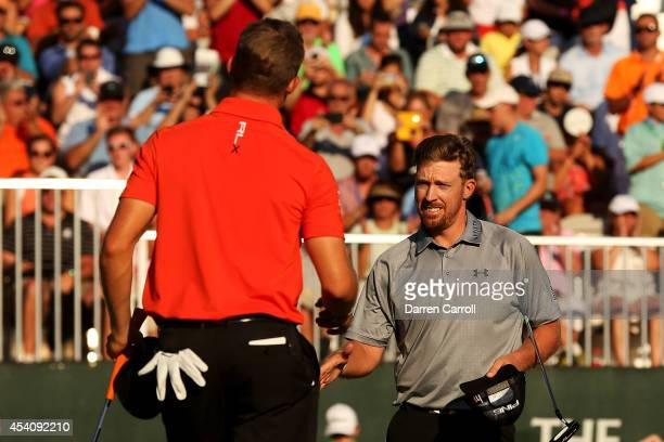 Hunter Mahan shakes hands with Morgan Hoffmann after they finished on the 18th green during the final round of The Barclays at The Ridgewood Country...