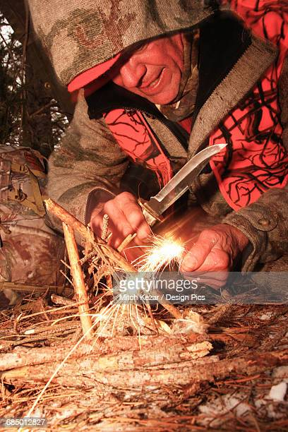 hunter makes a fire to survive in harsh weather - flint tool stock photos and pictures