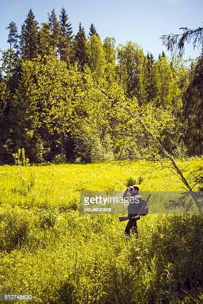 Hunter Observing a Green Field Through Binoculars
