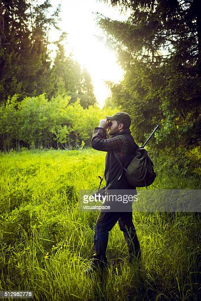 Hunter Observing The Distance With Binoculars In The Forest