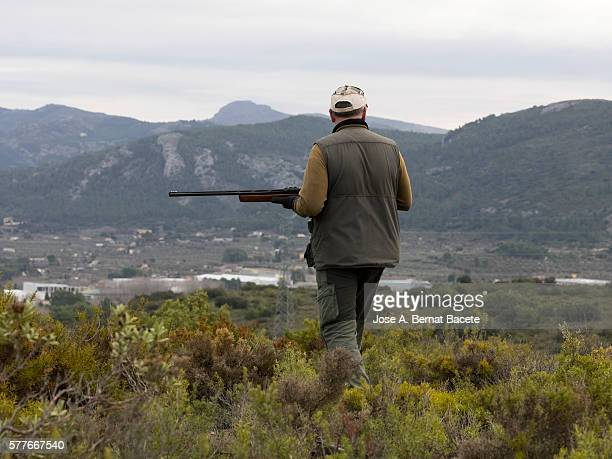 Hunter of partridges and rabbits, hunting in the mountains with his shotgun