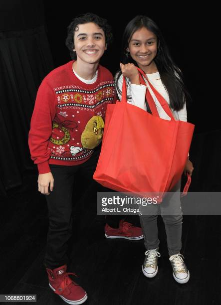 Hunter Payton poses with raffel winner Isabella Leon at the Hunter Payton And The Shoe Crew Holiday Charity Fundraiser Screening of Illumination's...