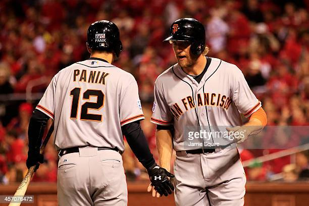 Hunter Pence celebrates with Joe Panik of the San Francisco Giants after scoring on an error by Matt Carpenter of the St Louis Cardinals in the...