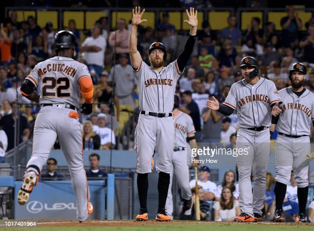 Hunter Pence, Chase d'Arnaud and Brandon Belt of the San Francisco Giants react as Andrew McCutchen comes home after a three run homerun to tie the...