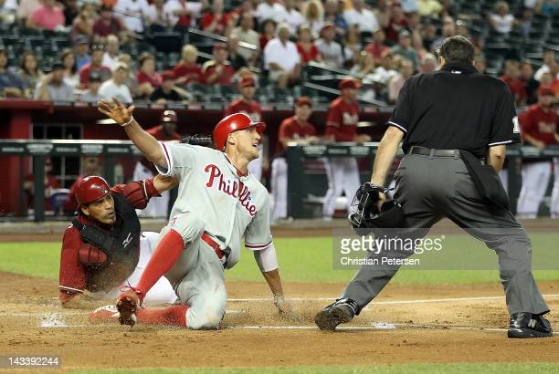 Hunter Pence of the Philadelphia Phillies is tagged out at home plate by catcher Henry Blanco of the Arizona Diamondbacks during the first inning of...