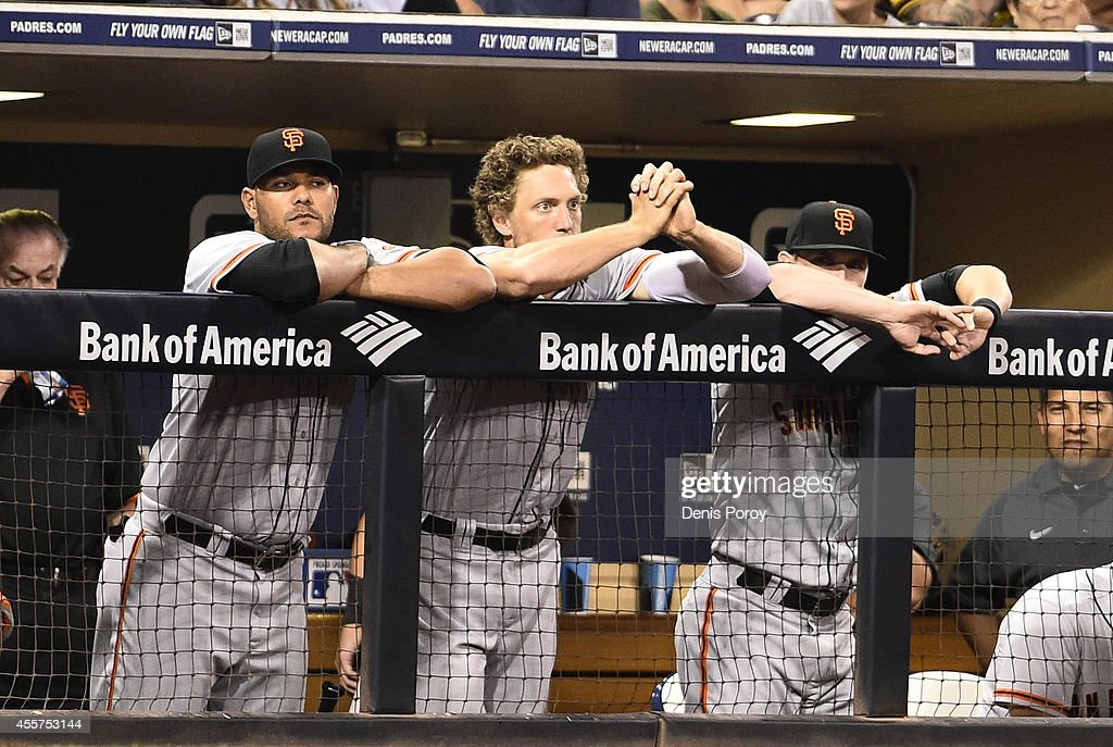 Hunter Pence #8 of the San Francisco Giants, center, clasps his hands as he looks out from the dugout during the eighth inning of a baseball game against the San Diego Padres at Petco Park September, 19, 2014 in San Diego, California.
