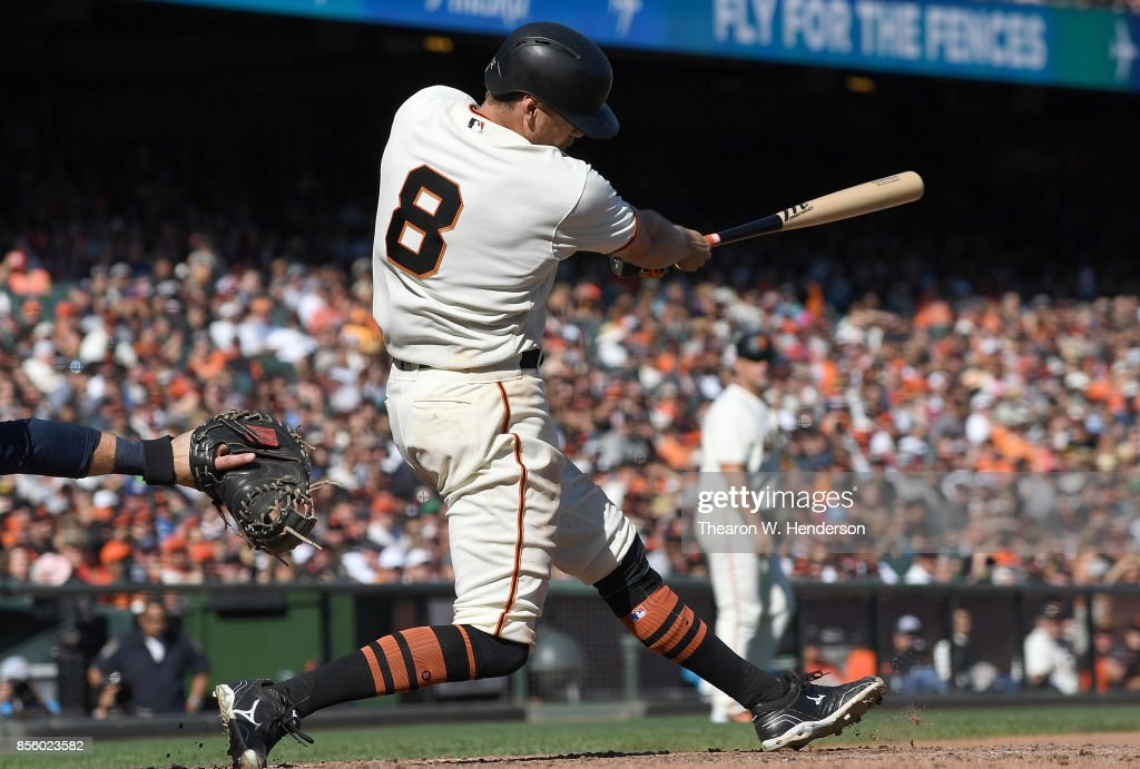 Hunter Pence #8 of the San Francisco Giants hits an RBI single scoring Ryder Jones #63 against the San Diego Padres in the bottom of the seventh inning at AT&T Park on September 30, 2017 in San Francisco, California.