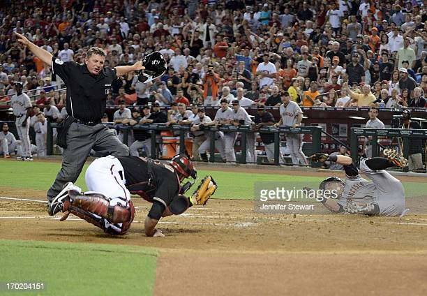 Hunter Pence of the San Francisco Giants is called safe at home plate on a throwing error made by catcher Miguel Montero of the Arizona Diamondbacks...