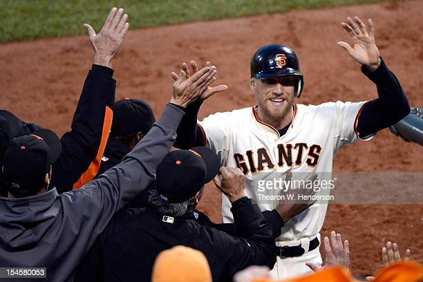 Hunter Pence of the San Francisco Giants is congratulated at the dugout after scoring in the third inning against the St Louis Cardinals in Game...