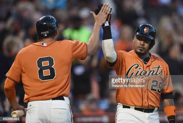 Hunter Pence of the San Francisco Giants is congratulated by Hector Sanchez after Pence scored in the bottom of the third inning against the Colorado...