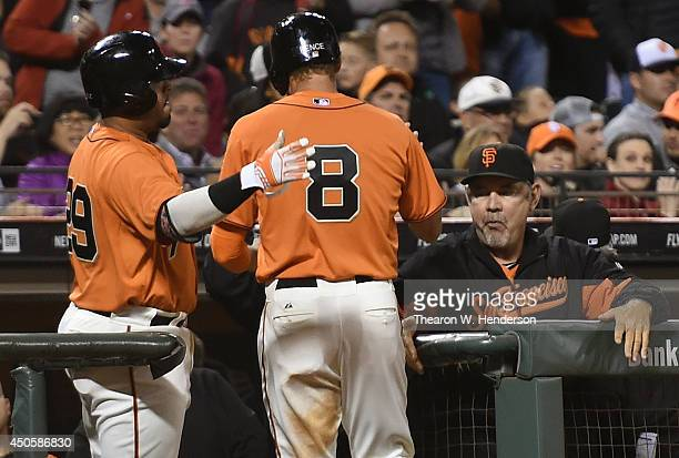 Hunter Pence of the San Francisco Giants is congratulated by Hector Sanchez and manager Bruce Bochy after Pence scored on a wild pitch in the bottom...