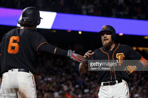 Hunter Pence of the San Francisco Giants is congratulated by Jarrett Parker after hitting a two run home run against the Arizona Diamondbacks during...