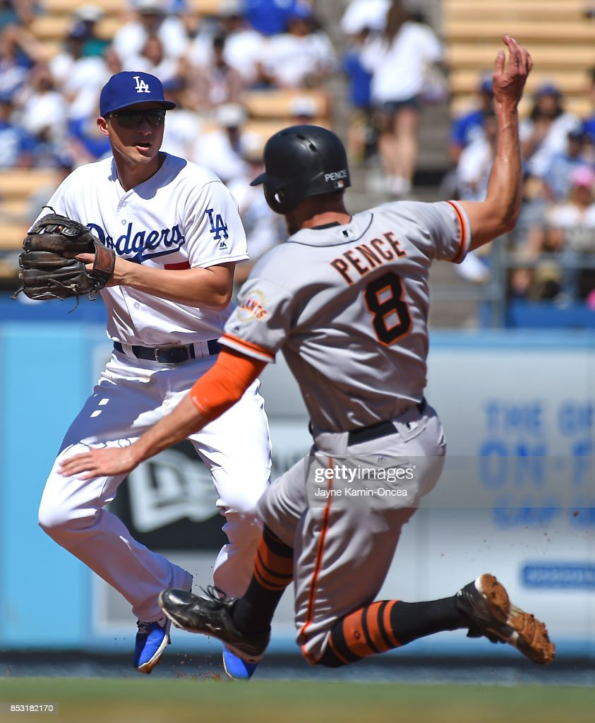 Hunter Pence #8 of the San Francisco Giants is out on a double play as Corey Seager #5 of the Los Angeles Dodgers throws to first to end the first inning of the game at Dodger Stadium on September 24, 2017 in Los Angeles, California.