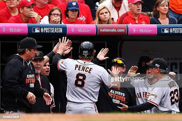 Hunter Pence of the San Francisco Giants is welcomed to the dugout after scoring on a single by Brandon Belt in the fourth inning against the...