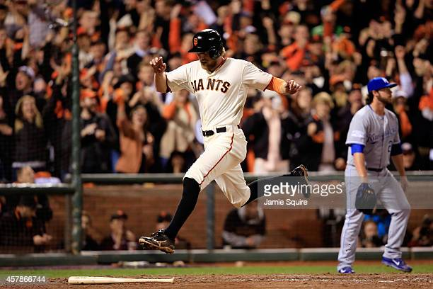 Hunter Pence of the San Francisco Giants leaps over the bat of Brandon Belt after scoring on a Belt single in the sixth inning against the Kansas...