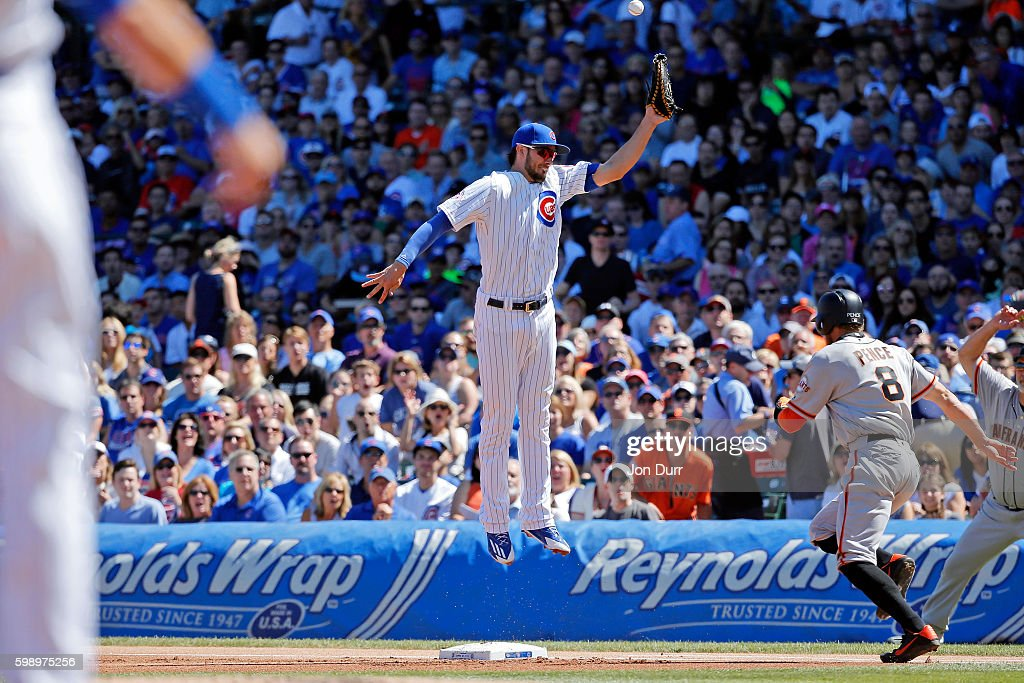 Hunter Pence #8 of the San Francisco Giants reaches first base as Kris Bryant #17 of the Chicago Cubs is unable to make a catch on a throwing error by Tommy La Stella #2 (L) during the first inning at Wrigley Field on September 3, 2016 in Chicago, Illinois.